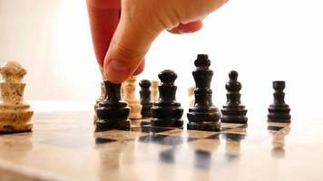 Chess board on a white background and a man making a move with his black queen video