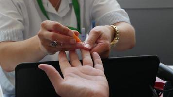 des images d'une infirmière poignarde et prélève du sang sur le doigt d'une personne afin de déterminer son groupe sanguin... video