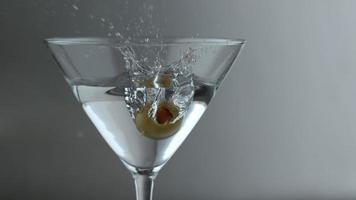 Slow motion shot of olive splashing into martini, shot on Phantom Flex 4K at 1000 fps video