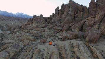 Aerial birds-eye view shot of a young man backpacker camping with his dog in a mountainous desert. video