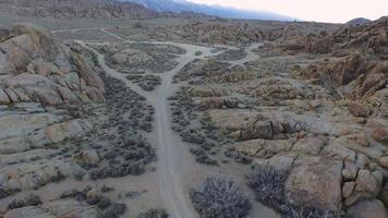 photo aérienne d'un jeune homme faisant de la randonnée avec son chien sur un chemin de terre dans un désert montagneux. video