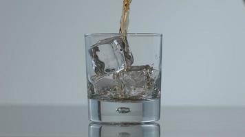 Whisky is poured over ice in slow motion, shot on Phantom Flex 4K at 1000 fps video