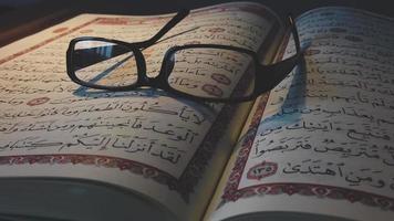 uma foto em movimento de um Alcorão aberto com óculos de leitura sobre ele video