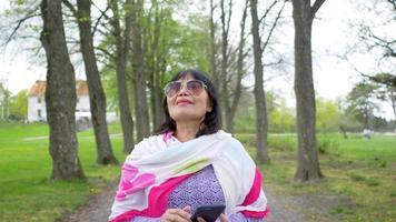 Cerrar la vista frontal del retrato al aire libre de una anciana asiática feliz con cara de sonrisa. caminar en el parque, sostener el teléfono y respirar profundamente en el parque. fondo de arboles grandes video
