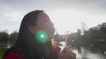 gros plan femme asiatique soufflant du pollen au bord de la rivière le week-end, s'amusant et s'amusant. prendre l'air avec une vue imprenable, une nature magnifique video