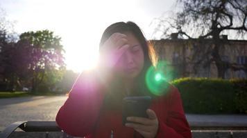 vue de face d'une femme asiatique aux cheveux raides noirs portant un manteau assis dans le parc, utilisant son téléphone pour discuter avec un ami et les cheveux lissants, simplement la journée, bon week-end video