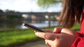 gros plan sur les mains d'une femme asiatique portant un manteau assis dans le parc au bord de la rivière et tapant sur son téléphone pour discuter avec un ami, belle journée, bon week-end, tapant le concept de smartphone video