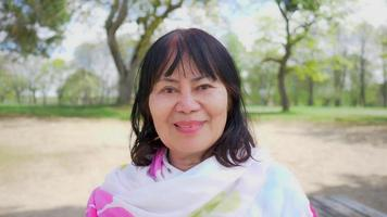 Close up outdoor portrait of a happy Asian old woman with straight hair and smile face. Standing at the park, getting some fresh air outside, relaxing and staying healthy video