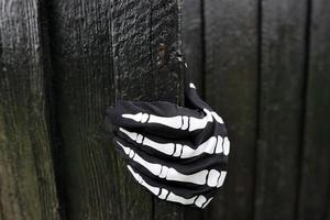 Black Wooden Door And Black Glove With Detail Of Human Skeleton Ornament. photo