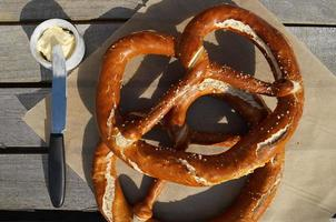 Big Pretzel, Butter And Knife On The Wood Table In The Garden. photo