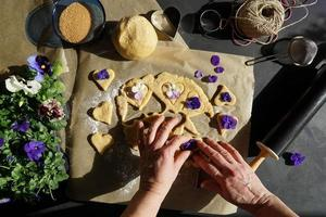 Woman Hands Making Cookies In Shape Of Heart With Heartsease Flower. photo
