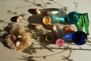 Easter Eggs In The Straw Nest And Decorative Colorful Glasses With Water On The Yellow-White Table. photo