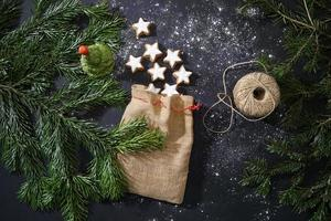 Festive Decoration, Traditional Cinnamon Cookies And Christmas Tree Branches On The Dark Table. photo