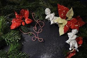 hermosa poinsettie rojo-blanco, ángel de cerámica y ramas verdes de árboles de Navidad. euphorbia pulcherrima, fondo floral festivo. foto