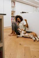 mujer joven negra hablando por teléfono celular y jugando a su perro foto