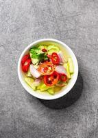 Rodajas de pepino, chile y cebolla en vinagre servido con moo satay, comida asiática foto