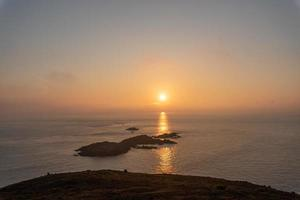 The sun rises from an island in the ocean photo