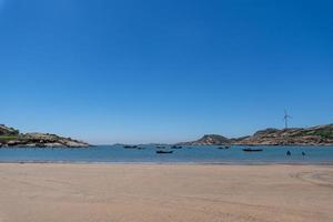 el mar bajo el cielo azul, playas limpias y agua de mar, así como islas y molinos de viento foto