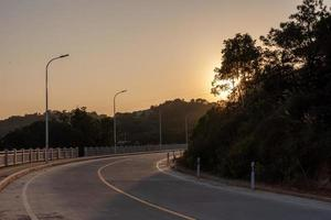 The dusk road leads to the distance, and the sky is golden photo