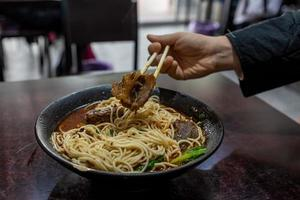 Pick up Chinese food with chopsticks photo