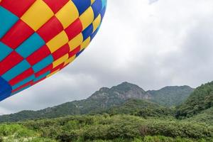 Close up hot air balloons with red, yellow and blue patches on the mountain photo