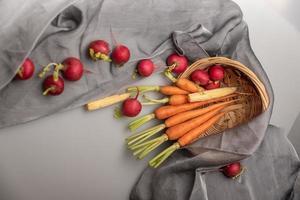 los rábanos rojos y naranjas están en la tela blanca foto