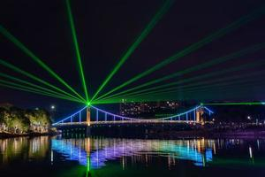 por la noche, el arroyo refleja las luces de colores en el puente foto