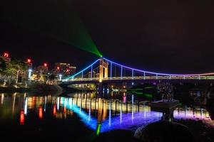 At night, the stream reflects the colorful lights on the bridge photo