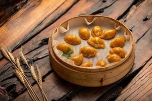 Platos tradicionales chinos para banquetes, albóndigas al vapor con piel de maíz. foto