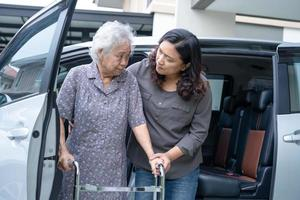 Help and support asian senior or elderly old lady woman patient walk with walker prepare get to her car, healthy strong medical concept photo