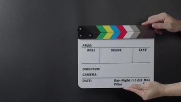 Movie slate or clapperboard hitting. Close up hand holding video
