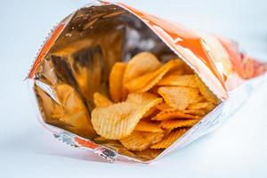 papas fritas, delicioso condimento para barbacoa picante para crips, bocadillo frito en rodajas finas, comida rápida en bolsa abierta foto