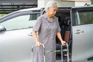 Asian senior or elderly old lady woman patient walk with walker prepare get to her car, healthy strong medical concept photo