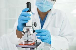 bioquímico científico asiático o microbiólogo que trabaja en la investigación con un microscopio en el laboratorio. para proteger brotes de coronavirus covid19, bacterias y gérmenes foto