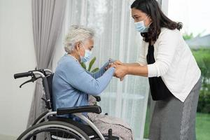 Help Asian senior or elderly old lady woman sitting on wheelchair and wearing a face mask for protect safety infection Covid-19 Coronavirus photo