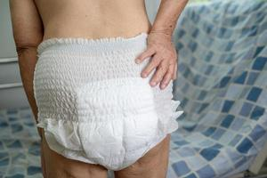 Asian senior or elderly old lady woman patient wearing incontinence diaper in nursing hospital ward, healthy strong medical concept photo