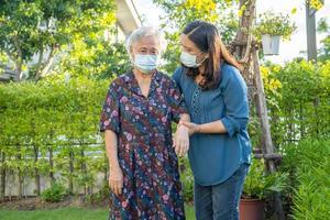 Anciana asiática con cuidador caminando con feliz en el parque natural foto