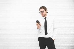 Businessman in formal uniform and using smartphone or mobile phone in front of white wall, Business and fashion concept. Cross processing and Split tone instragram like process photo