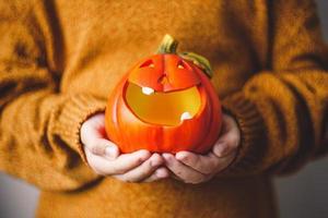 Lámpara de calabaza de Halloween en manos de los niños. foto