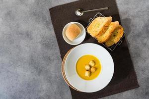 sopa de calabaza con crutones de pan en un plato de pan de ajo foto