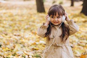 Little girl listening to music on headphones in the autumn park photo