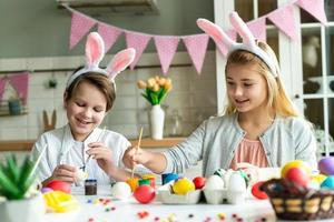 Two happy children in bunny ears paint Easter eggs at the table. photo
