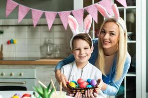 mamá sonriente con hijo posando sosteniendo huevos de Pascua en orejas de conejo. foto