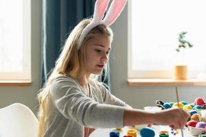 Smiling blond girl paints Easter eggs. Side view. photo