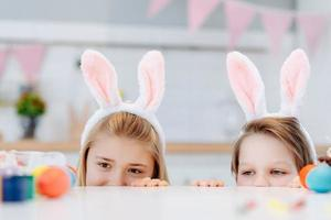 Two children look out from under the table, look at Easter eggs. Have fun in the kitchen. photo