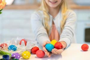 chica sosteniendo huevos de pascua de colores en su mano. de cerca. foto