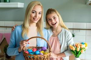 mamá e hija sosteniendo una canasta de huevos de pascua. foto