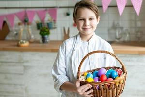 Close up of smiling boy with basket of Easter eggs. photo