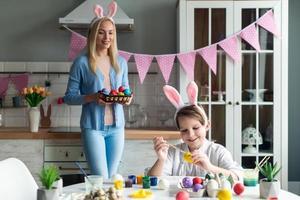 hijo está pintando huevos de Pascua, mamá está mirando y sosteniendo una canasta. foto