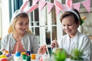 Two joyful children paint easter eggs in rabbit ears. photo